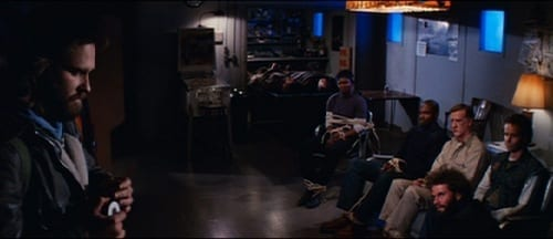 MacReady stands across the room heating the wire to use for blood testing, as the other men sit tied to the couch on the other side of the room.