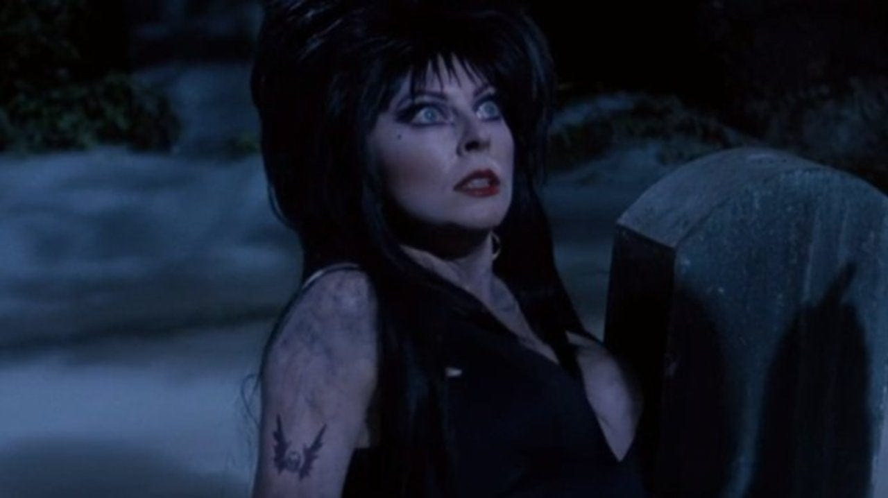 Elvira, on the ground, in a dark and foggy cemetery with a look of terror on her face.