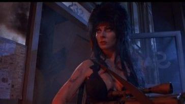 Elvira stands alone holding a machine gun outside, at night.