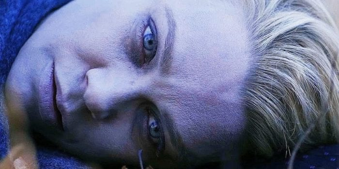 Laurie Holden as Mrs. Reyes' vacant, bluish face lying horizontally on the forest floor.