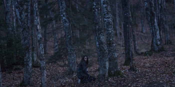 Leah kneels and looks around in the woods, preparing for her ritual