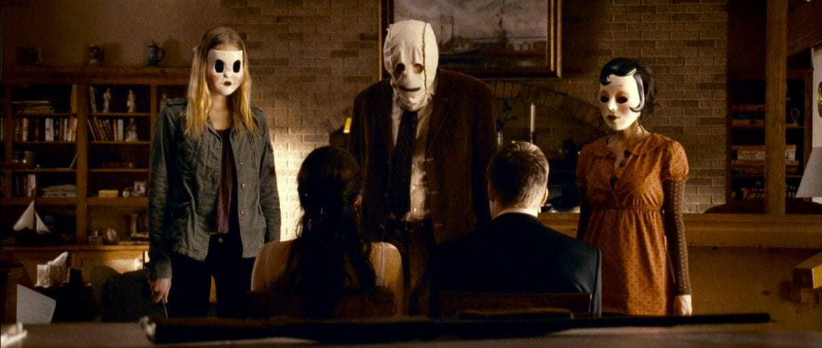 The three masked strangers stand in front of the bound Kristin and James