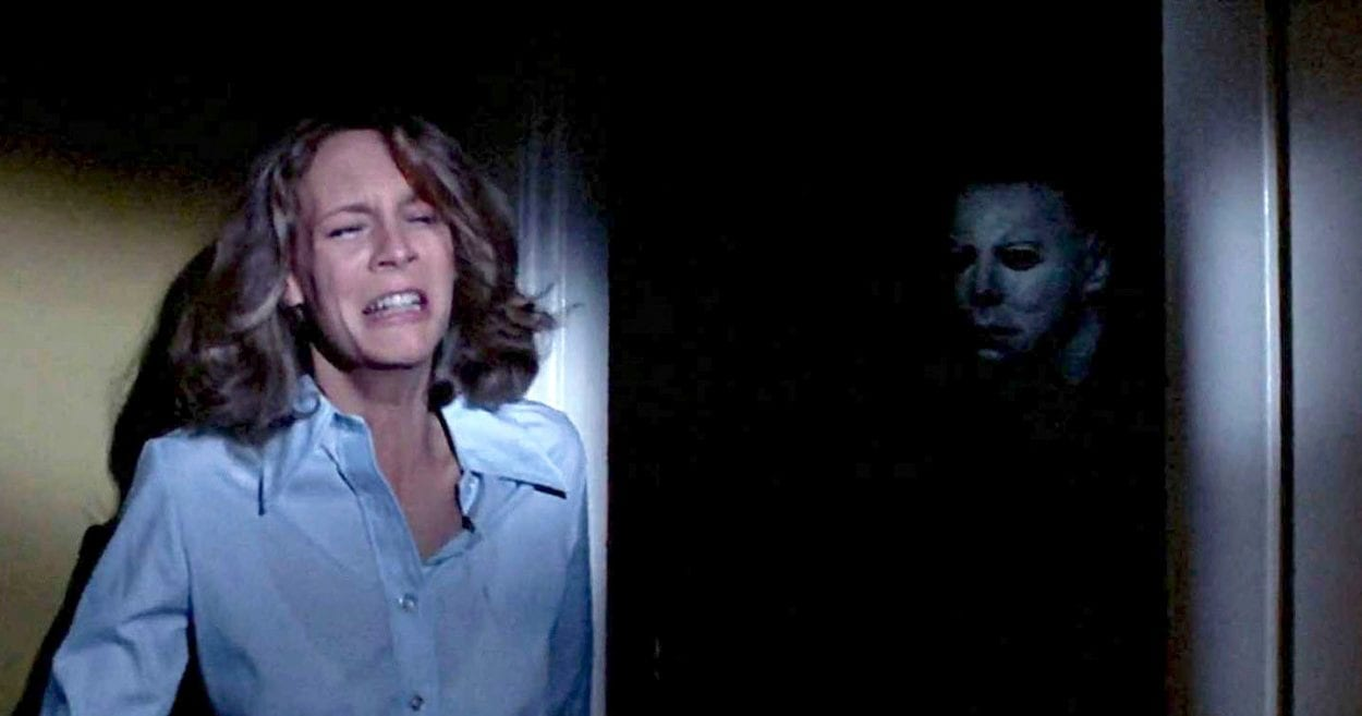 Michael Myers stalking Laurie Strode from the shadows of a darkened room