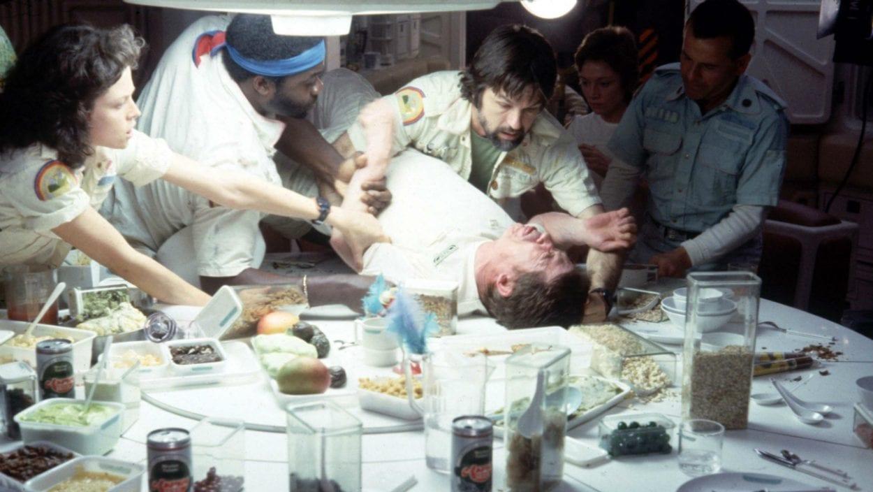 Sigourney Weaver, Yaphet Kotto, Tom Skerritt and Ian Holm hold John Hurt down.