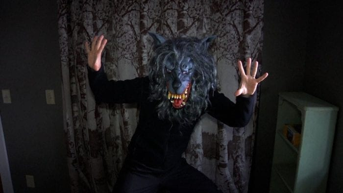 A man wearing a wolf head mask, dressed in all black, stands in the center of a room with his hands up.