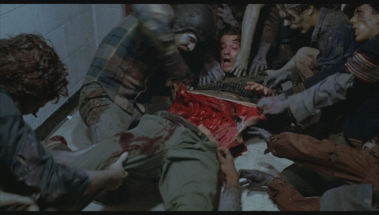 A man lies on the ground surrounded by zombies who are tearing into his flesh, ripping his torso apart