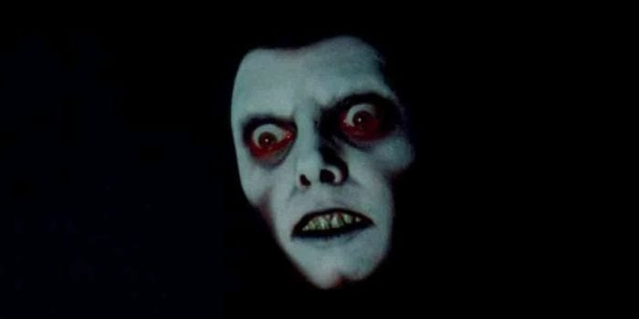 A white face with elaborate black and red makeup around the eyes peers menacingly from the dark.