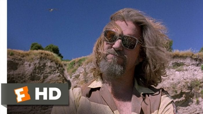Jeff Bridges as The Dude, his face, beard, hair and sunglasses covered in Donny's ashes after a wayward gust of wind.
