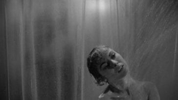Marion Crane showering in the foreground, while behind the shower curtain, a figure approaches in the background.