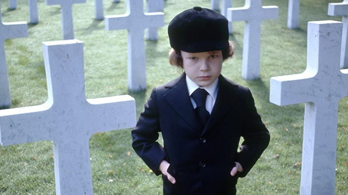 Damien, the antichrist child stands in front of graves