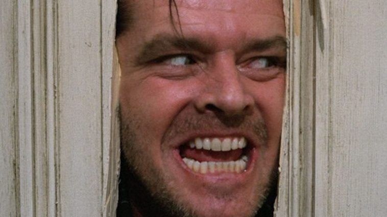 Jack Torrance peers through a broken door with a crazed look on his face