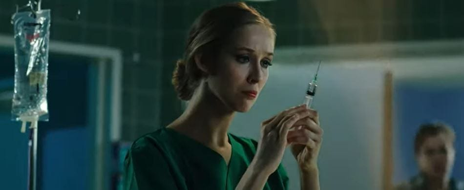 Nurse prepping patient in OR with a syringe