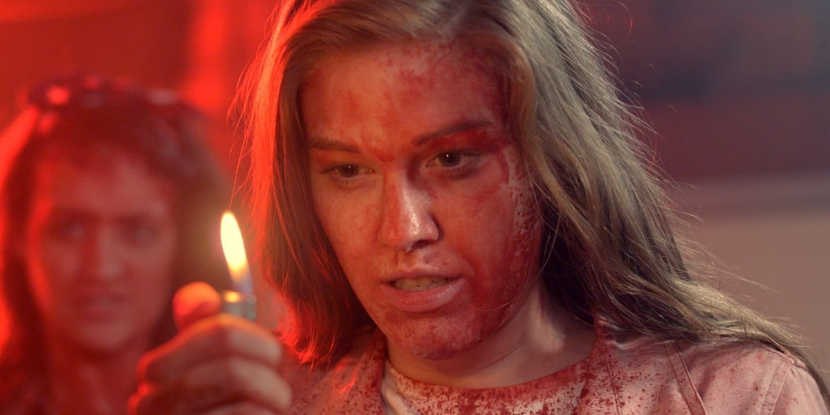 Daisy setting stares into the flame of a lighter in her hand with blood smeared on her face as friend looks on uneasily from the background.