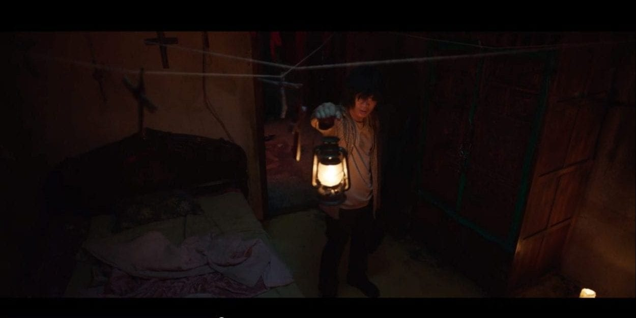 disheveled man holding a lantern in front of him - over his head several crosses hang from string