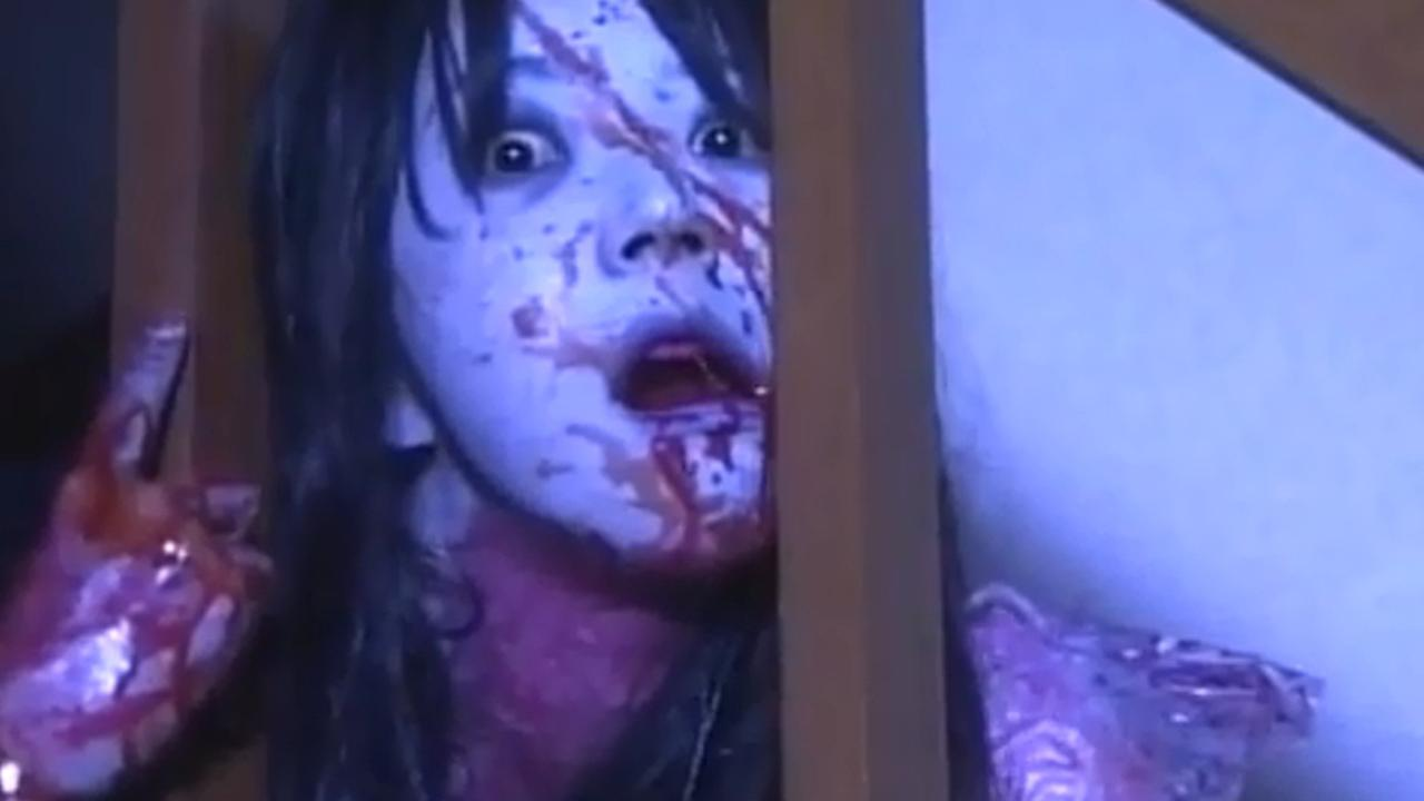 Young woman with vacant star looks through staircase banister with blood covering face and hand.