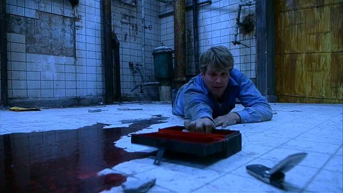 Man desparately reaches for box with saw on bathroom floor next to pool of blood with boarded entrance