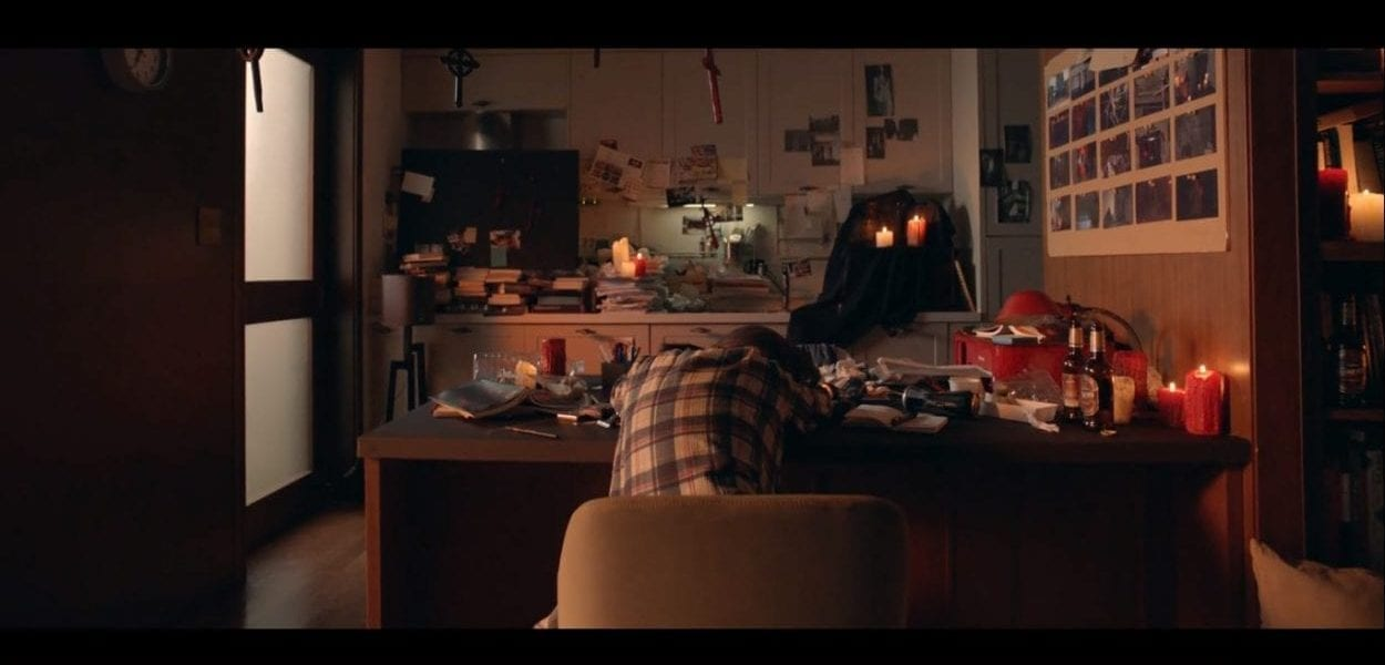 shot from behind of a person laying their head on a cluttered desk over their head hangs multiple crosses