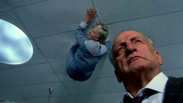An elderly man looks off camera in the foreground. In the background, a woman clings to the ceiling, like an insect, watching him.t