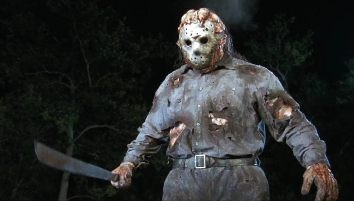 Jason standing in the woods holding a machete