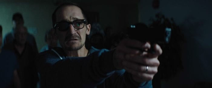Man with glasses looks nervous and points a gun.