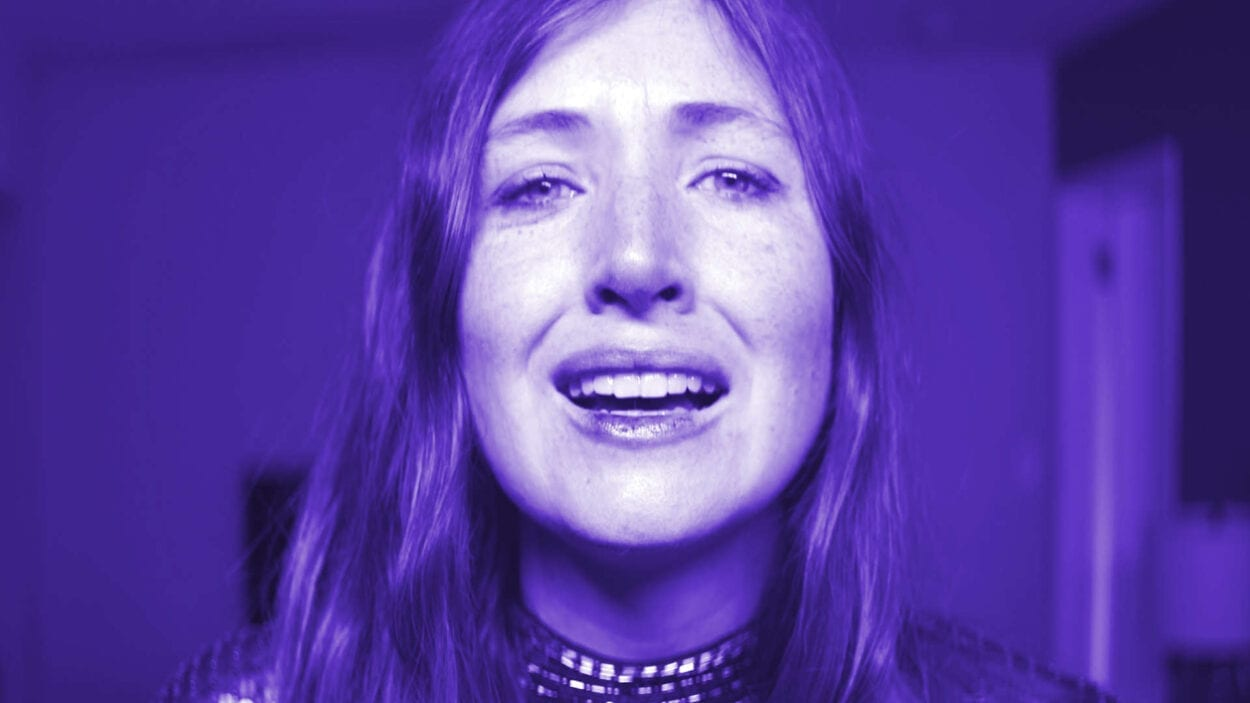 a white brown haired woman - actress kate lyn sheil - looking at the camera with a pained expression while bathed in otherworldly purple light