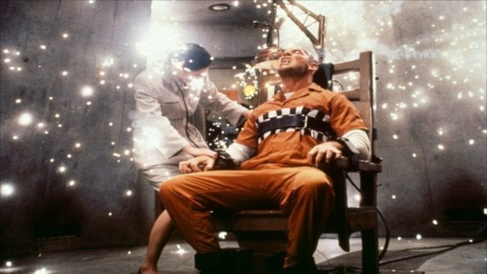 One man is strapped into an electric chair while another man stands over him, the chair is throwing sparks.
