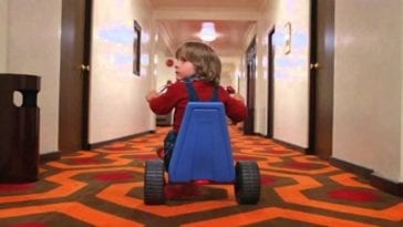 Danny Lloyd as Danny Torrance looks over his shoulder uneasily as he pedals down the hotel hallway on his tricycle.