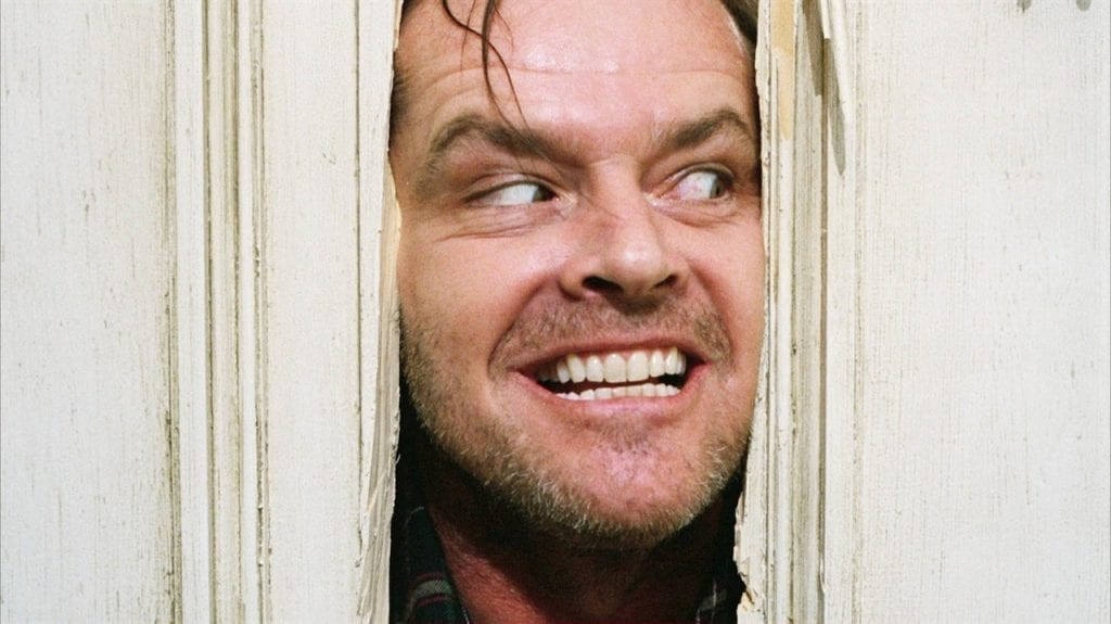 "Close up of Jack Nicholson as Jack Torrance grinning as he thrusts his face through broken door in iconic ""Here's Johnny"" shot."