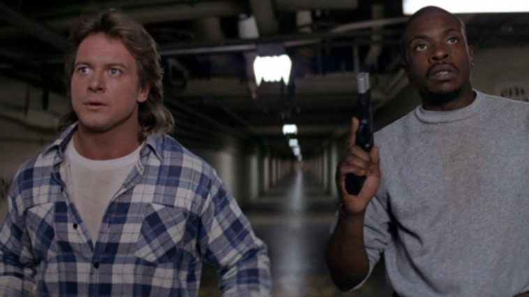 Two men stand in a long hallway, one with a gun in his hand.