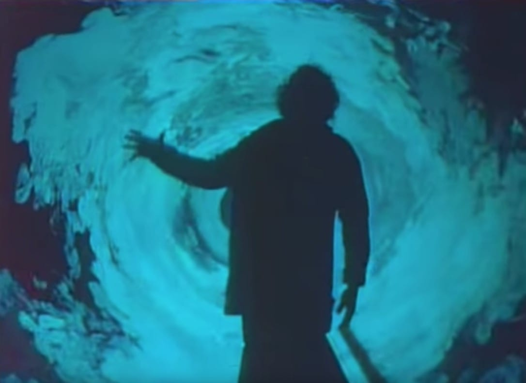 A person in silhouette in front of a swirling vortex of blue-lit smoke