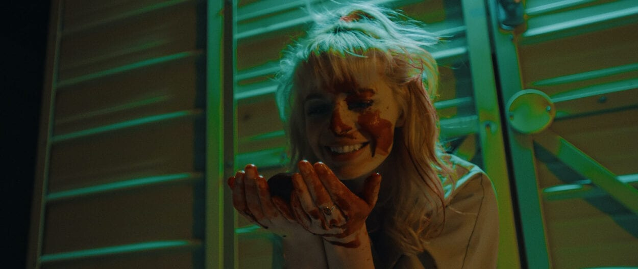 Regina (Chloe Farnworth) laughs, staring at her blood-soaked hands in an alley-way in green neon light.