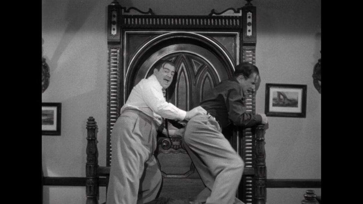 "Wilbur Grey (Lou Costello) and Chick Young (Bud Abbott) brace their shoulders against a door as they barricade it with a bed in the film, ""Abbott and Costello Meet Frankenstein"" (1948)."