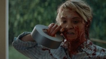 May (Brea Grant) rips some duct tape with her teeth as she's covered in blood
