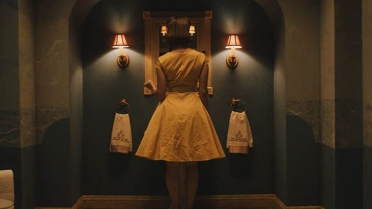 Emma (Christine Kilmer) wearing a 50s style yellow dress, faces a mirror in a bathroom.