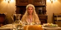 """Robyn Nevin as """"Edna"""" sits at the head of a dinner table"""
