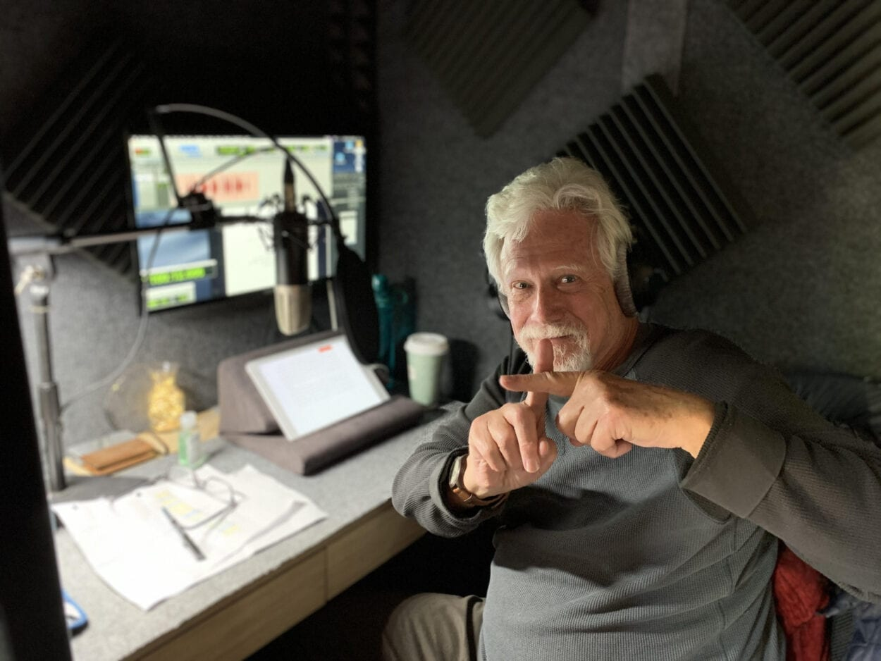 An older man sits in front of a monitor and microphone making a cross with his index fingers playfully warding off the photographer