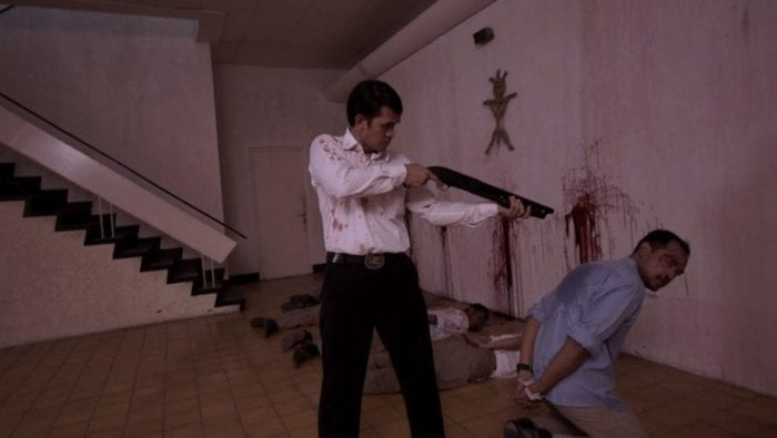 A man points a shotgun at another kneeling man. A bizarre symbol painted in blood adorns the wall and corpses of other executed prisoners lie on the ground