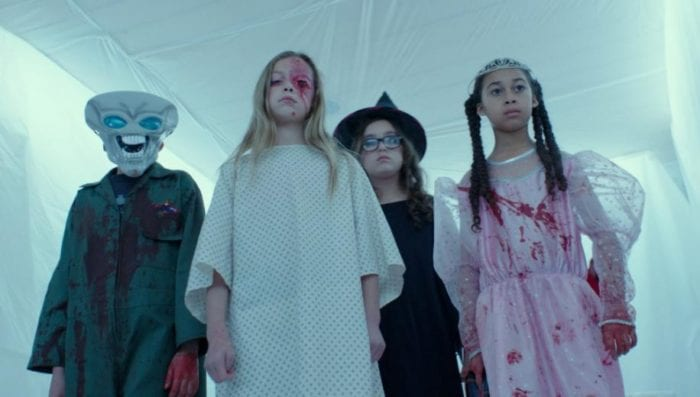 A group of blood covered trick or treaters stand in a room covered in plastic sheets.