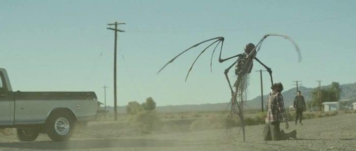 A bizarre demon shoves its arm down a man's throat on a desert road
