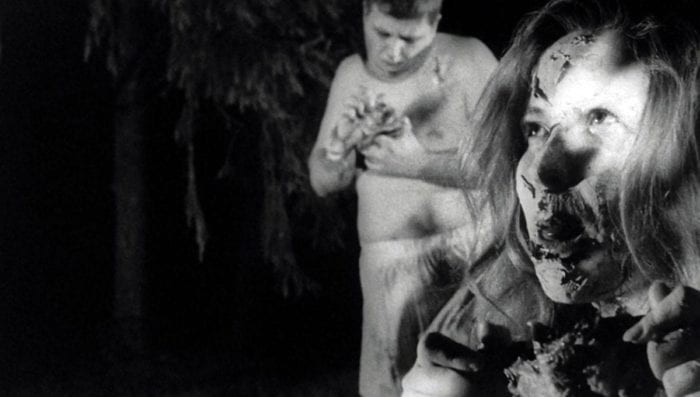 Close-up of an undead woman's disfigured face as she eats a bit of human remains; in the background, standing, a shirtless male ghoul examines the chunk of flesh he holds in his hands.