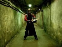 A man wearing a metal mask wields a chainsaw in a dark, dingy hallway.