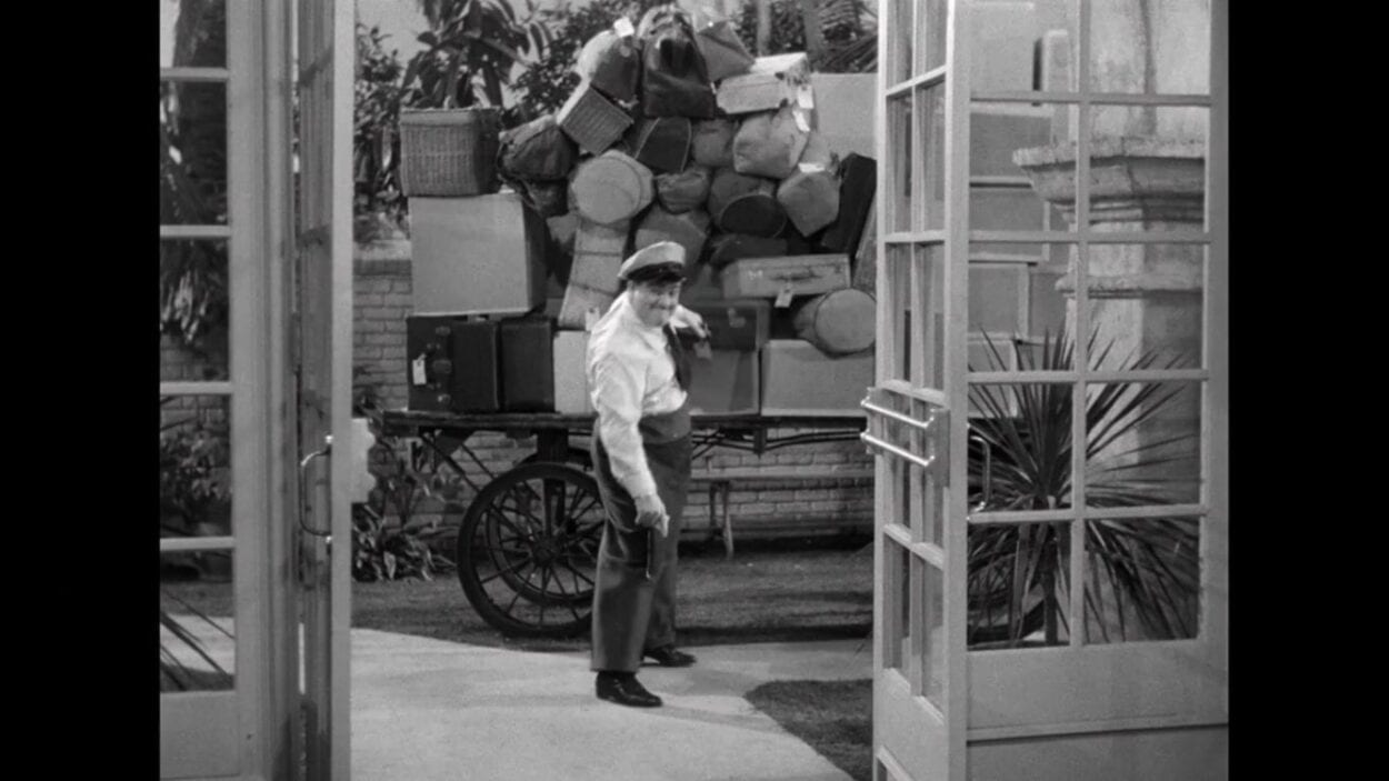 "Wilbur Grey (Lou Costello) pulls a grip out of a pile of baggage in the film, ""Abbott and Costello Meet Frankenstein"" (1948)."