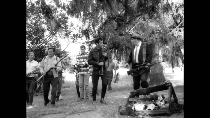 A group of men, all armed with rifles, make their way through a field, past trees and burnt debris strewn on the ground.