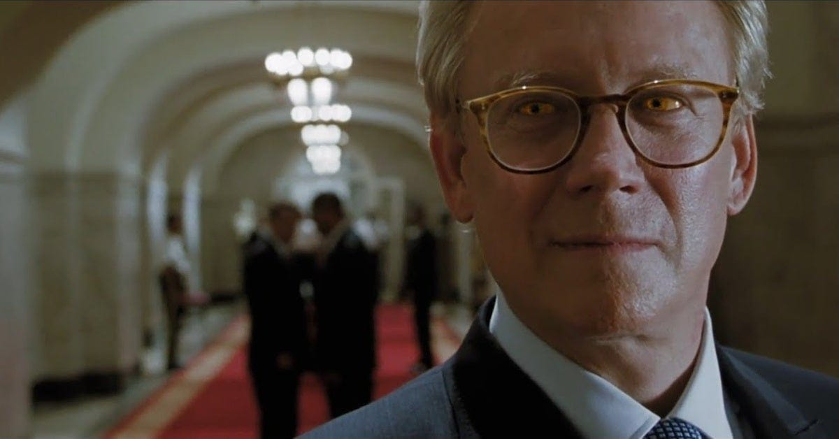 a middle aged man in close up standingf in a hall of congress staring towards the camera with reptilian eyes