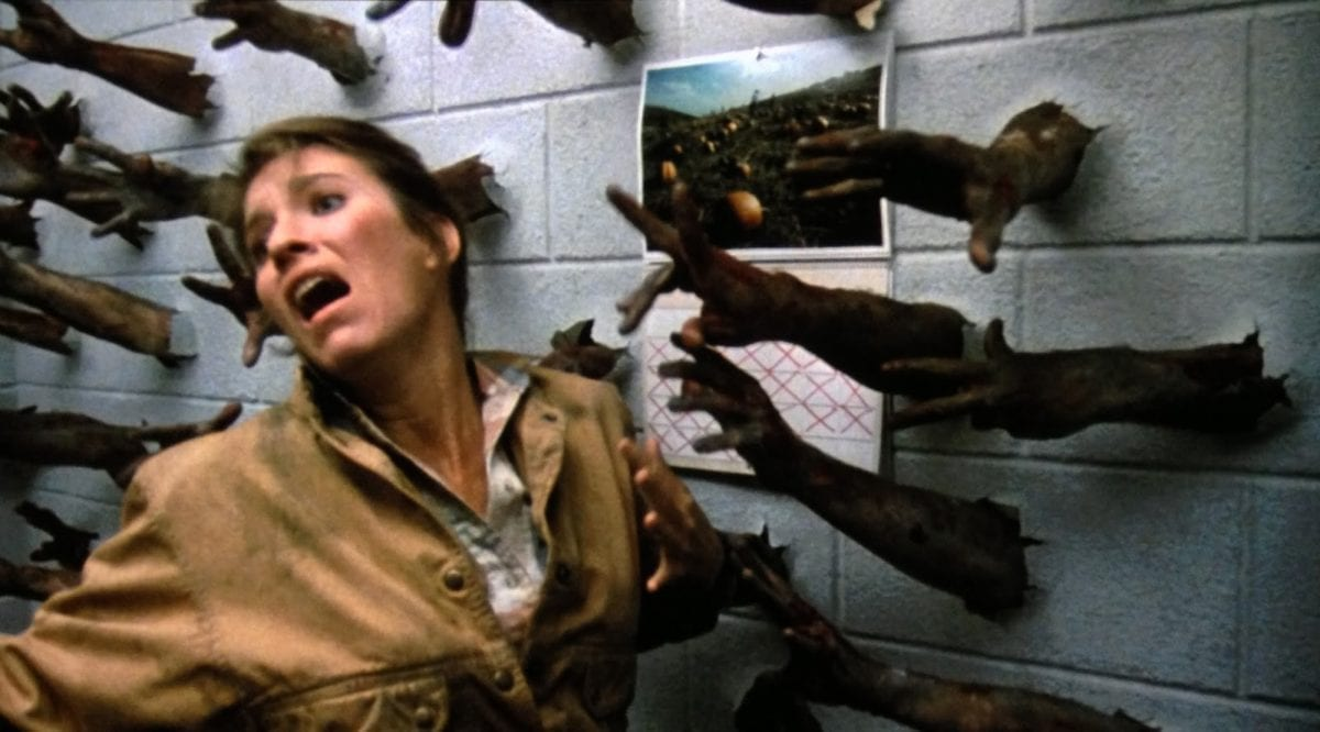 A woman in a tan jacket wrenches herself away from a concrete wall that has rotting, zombie hands burst through it and reaching for her.