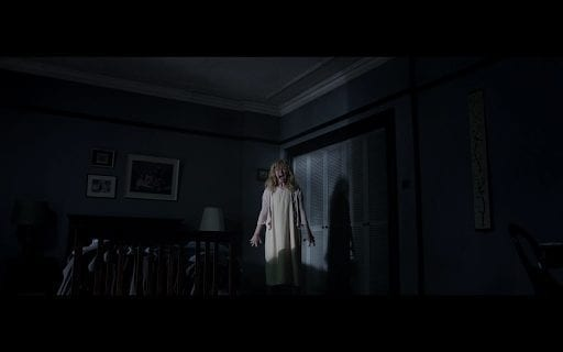 A woman stands, barely illuminated, in a dark room, in her pajamas.
