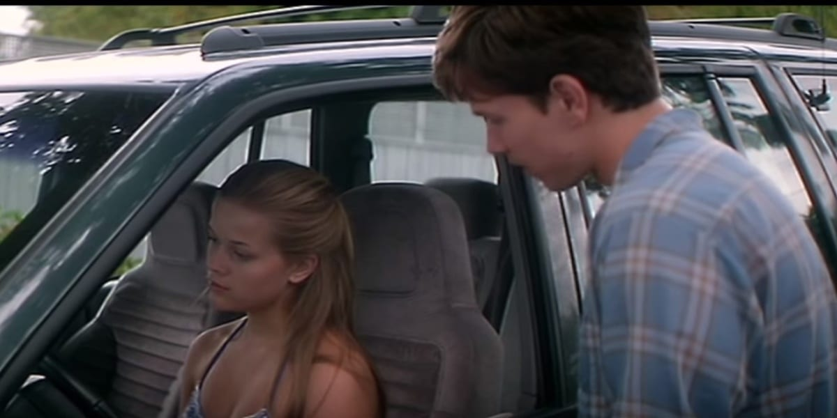 David standing before her, apologizing to Nicole, who stares ahead looking hurt and angry in the driver's seat of her Jeep, in Fear