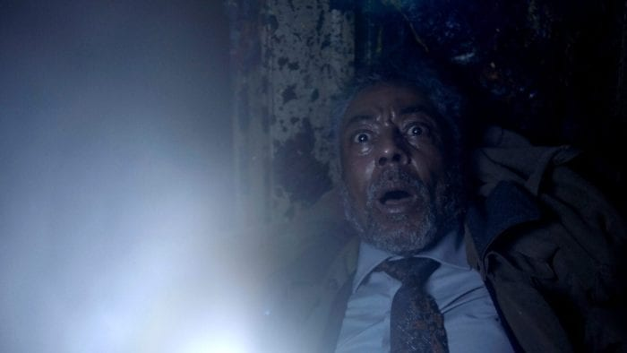 A man stands in a dark room while holding a flashlight. The man has a startled expression on his face.