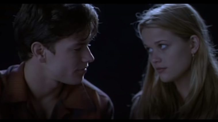 Nicole looking at David uncertainly in Fear, as he looks back at her lovingly with a dark background