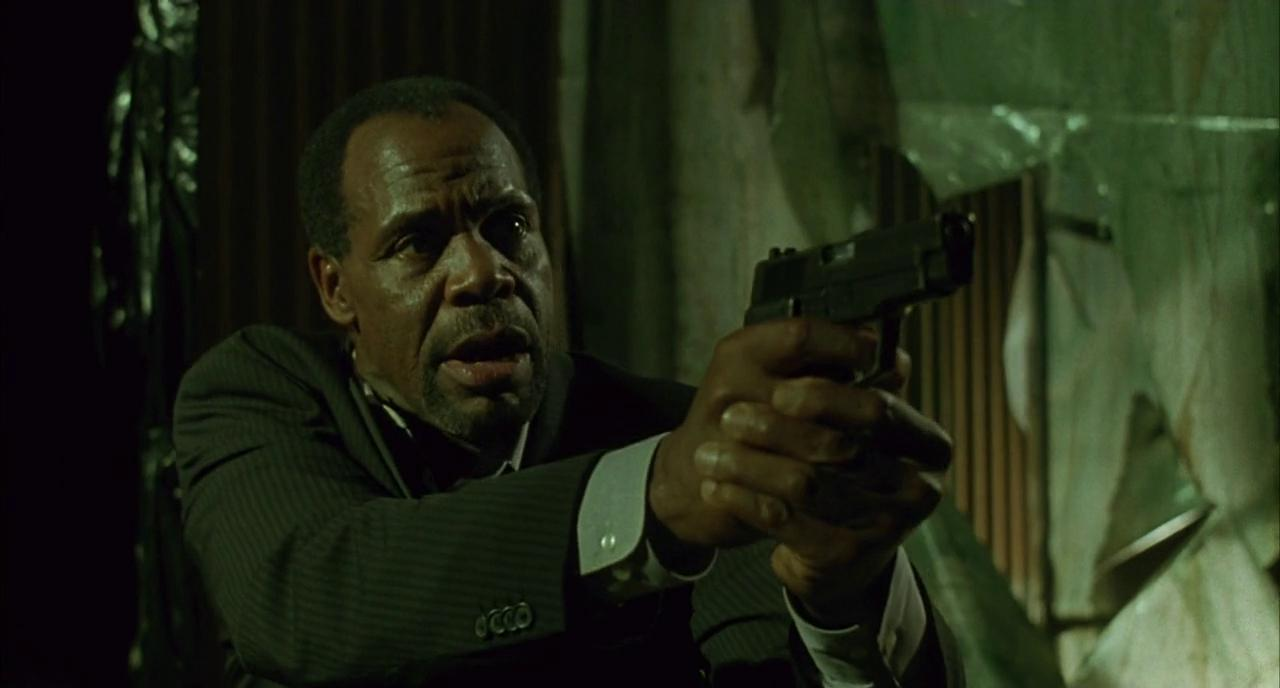 Detective Tapp holding a gun in Saw.